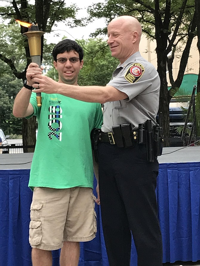 At the inaugural Law Enforcement Torch Run for Special Olympics Virginia at Reston Town Center held on Saturday, July 21, 2018, athlete Joey Wheeler of Lorton accepts the Flame of Hope from Colonel Edwin C. Roessler Jr., Chief of Police, Fairfax County Police Department, before the start of the run.