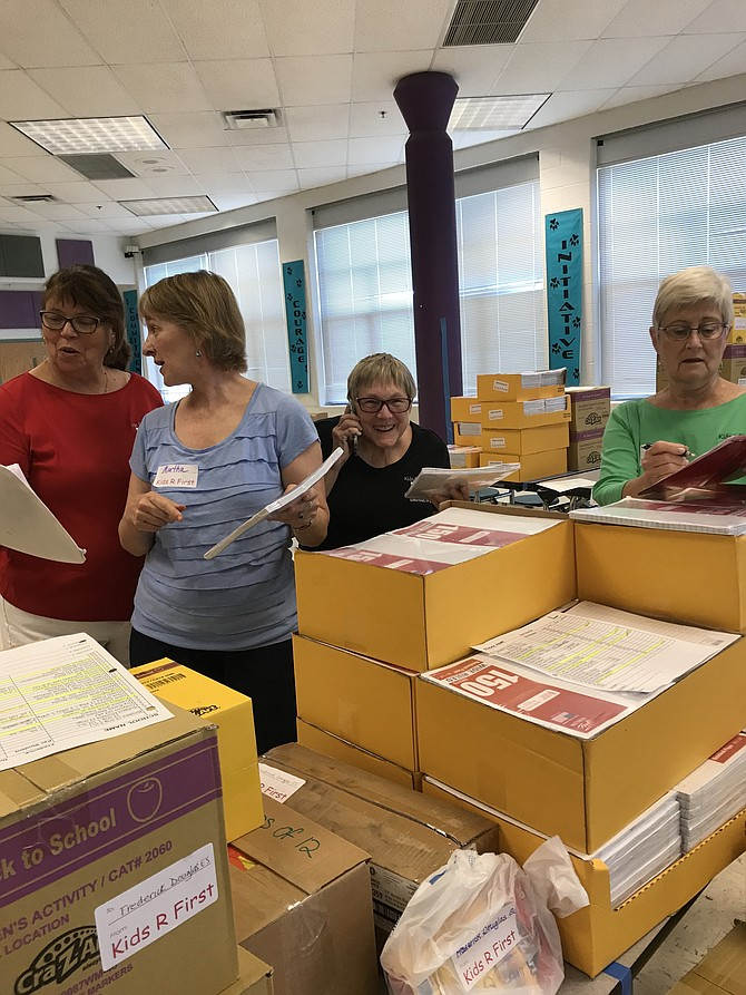Kids R First (KRF) volunteers Valerie Warriner, Martha Chamberlin, Patty Gehring, and Susan Ungerer, CEO and Founder of KRF, pack up donated school supplies for needy public school children in participating Fairfax and Loudoun County Schools.