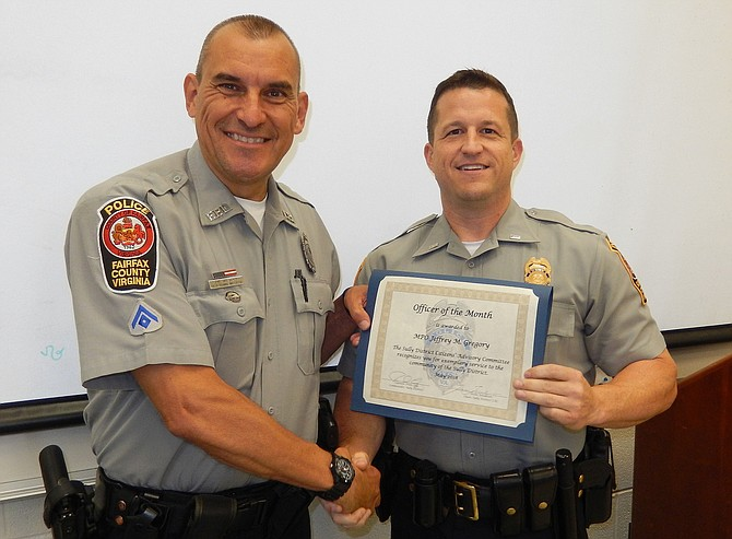 From left: MPO Jeffrey Gregory receives his Officer of the Month certificate from Sully District Station Assistant Commander Ryan Morgan.