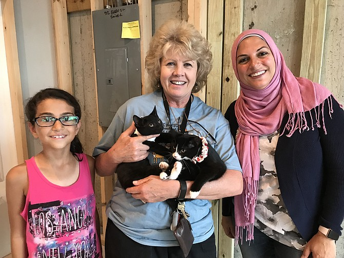 (Center) Christine Cozza from 4 Paws Rescue Team brings a couple of kittens to the future site of Meows Corner, a cat café in Herndon. Dina Abdel-Hamid of Herndon, owner of Meows Corner, and her daughter Mariam Hawa, 8, are excited as the build-out of Meows Corner nears completion.