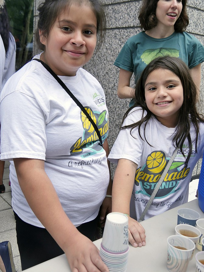 Ten-year-old Brittaney Medina and her eight-year-old sister, Mia, serve cups of lemonade at the Bridges to Independence stand on Aug. 2 at FARMFRESH at Ballston Market.