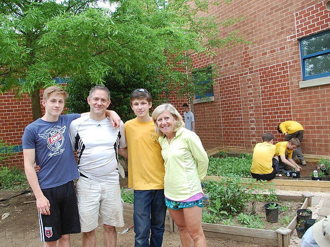 From left: Ethan Himes, dad Michael Himes, Caleb Himes, and Kent Gardens Elementary School Principal Holly McGuigan at the Monarch Waystation at the school.