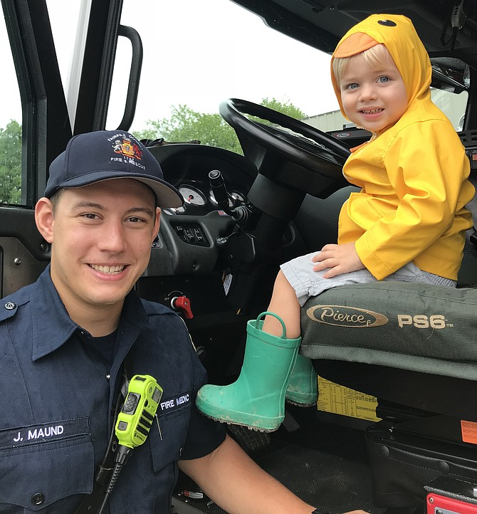 "Fire Medic Jake Maund of Fairfax County Fire and Rescue, #425 Reston spots Beckett Wilson, 2 1/2 of Fairfax, as he sits in one of the County's fire engines and tries out the steering wheel during Reston Association's annual ""Totally Trucks"" event held this year on Friday, Aug. 3, 2018."