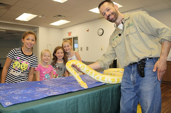 The albino python is hit with Reagan Silver, Harper Gillespie, Lilly Silver and Jillian Gillespie and handler Turk Ozerol of My Reptile Guys.