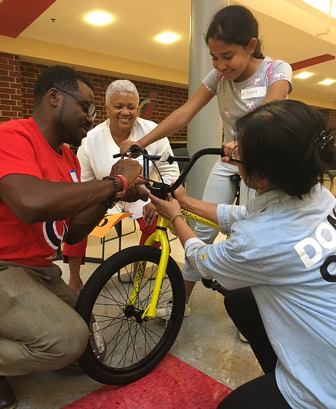 Alexandria City Public Schools Chief Operating Officer Mignon Anthony, and ACPS staff present Naria with a new bicycle.