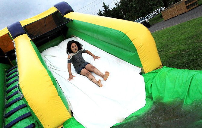 A girl rides a water slide at National Night Out at the Conservatory at Four Mile Run.