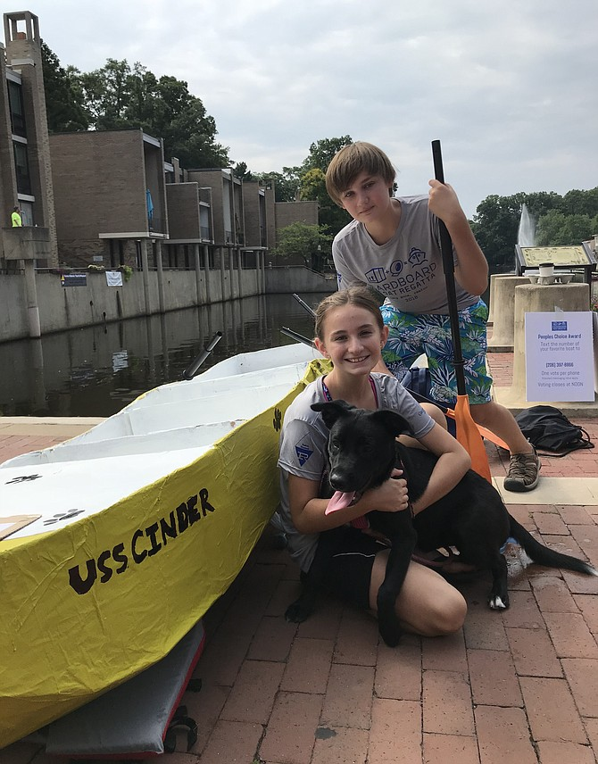 "Pirates Lea Daniel, 11, from Great Falls and her brother, Quincey, 14, prepare to launch ""USS Cinder"" at the 2nd Annual Lake Anne Cardboard Boat Regatta held Saturday, Aug. 11. The team placed first in the Cadet Class with a time of 2:14."