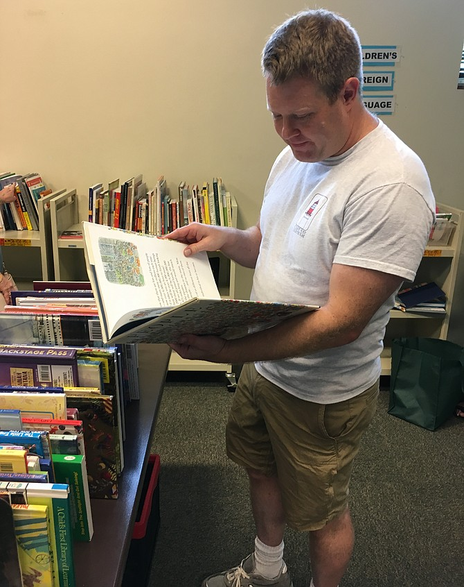 Cameron Rittenhouse-Smith browses the children's book section at the Potomac Library Book Sale on Saturday, Aug. 11. He said he started a program to give books to children in foster care in Washington County, Md.