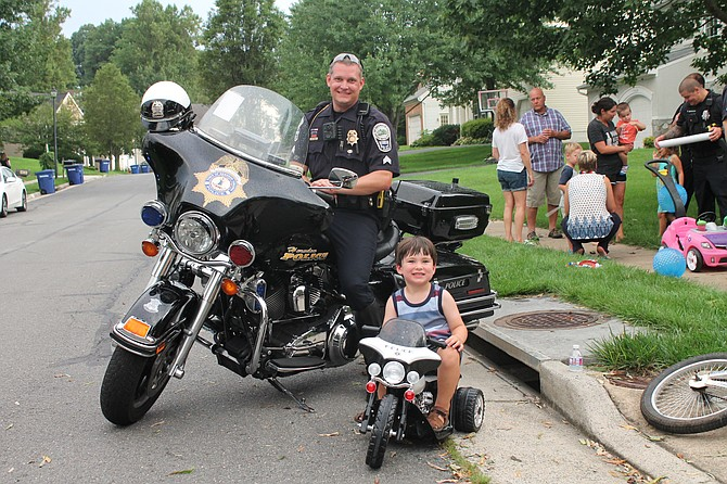 It's kickstand down for Sergeant Jim Rider of Herndon Police Department as he pulls up alongside his future replacement during National Night Out 2018 in the Town of Herndon.