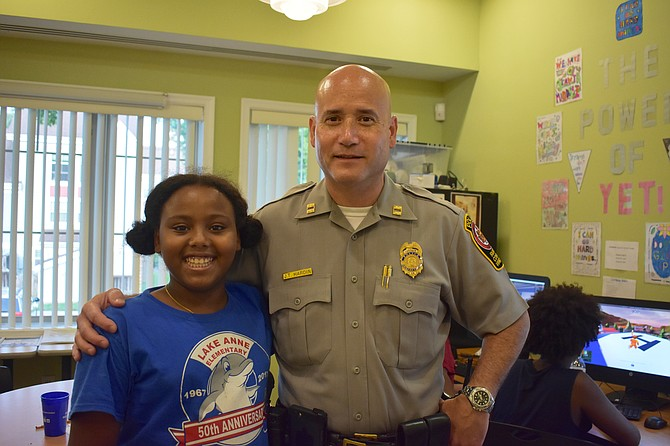 Ten-year-old Yumna Ahmed meets Captain Jack Hardin of the Reston District Police Station at her neighborhood's National Night Out event Aug. 7.