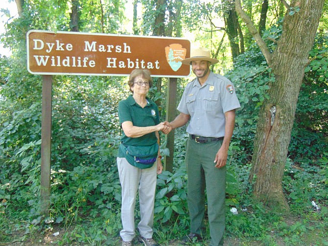 Commemorating the announced start of Dyke Marsh restoration are Dorothy McManus, board member, Friends of Dyke Marsh, and Chief of Staff of U.S. National Park Service Aaron Larocca at the entrance to Dyke Marsh Wildlife Preserve on Aug. 8.
