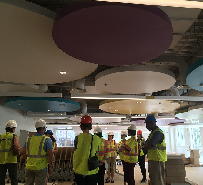 "City and school employees tour the first floor cafeteria. The setup, once complete, will include small tables for a ""family feel,"" said Principal Rachael Dischner."