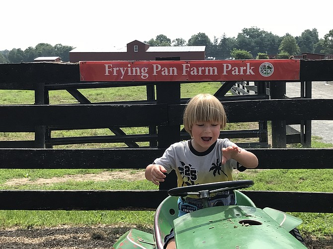 Raphael Schafer, 4, of Burke tries out the tractor at Frying Pan Farm Park in Herndon on a beautiful morning in August.  Frying Pan Farm Park is a sought-after destination for the young and old, not only residents in Herndon and the Town of Herndon, but throughout Fairfax County.