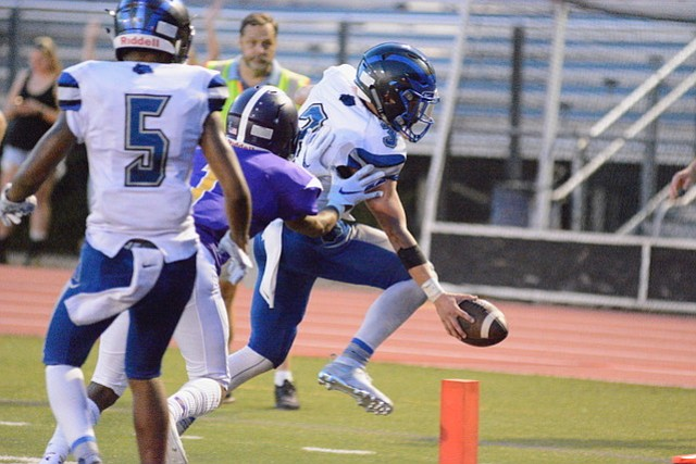 West Potomac quarterback JT Mayo reaches the ball over the goal line for one of his three rushing touchdowns against Lake Braddock on Aug. 31.