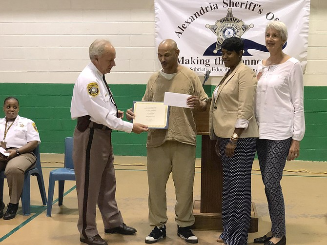 Sheriff Dana Lawhorne, left, presents the third place poetry award to Daryl Torien at the Aug. 16 HEARDS Creative Writing Awards ceremony at the William G. Truesdale Detention Center. With Lawhorn and Torien are Gloria Wright, director of inmate services, and HEARD founder Jane Collins.