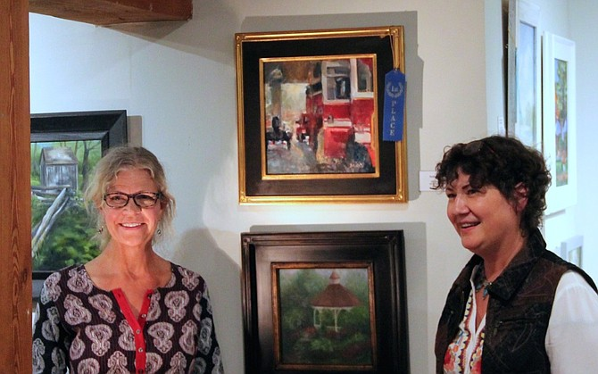 "Jill Banks stands next to her winning painting ""Station 12"" with competition judge Lynn Mehta."