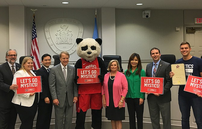"Celebrating Fairfax City's temporary name change this week to ""Mystic City"" are (from left) Council members Michael DeMarco, Jennifer Passey and Sang Yi, Mayor David Meyer, Pax the Panda, Council members Janice Miller, So Lim and Jon Stehle and a Mystics representative."