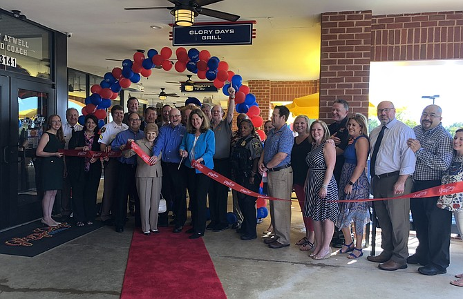 Mayor Allison Silberberg, center with scissors, leads a crowd of dignitaries and supporters in cutting the ribbon to officially open Glory Days Grill Sept. 6 in the Alexandria Commons Shopping Center on Duke Street. The location is the company's 33rd and 15th in Virginia.