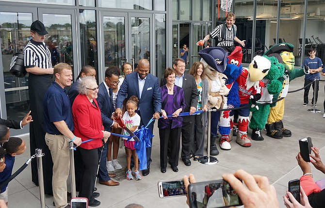 The St. James co-founders Kendrick Ashton and Craig Dixon, with scissors, are joined by local and state politicians Sept. 15 for the official ribbon cutting grand opening of The St. James sports and wellness complex in Springfield.