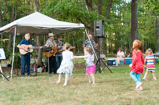 Children take a break from pumpkin painting to dance with the bluegrass music of the Andrew Acosta Band.