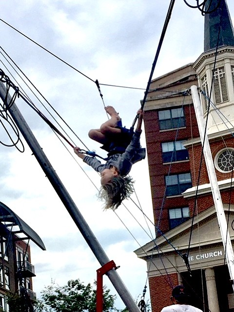 """Push hard with your legs."" Youngsters who waited in line for more than half an hour soar into the air on the bungee bounce at Kids Zone on Clarendon Day Saturday, Sept. 22."