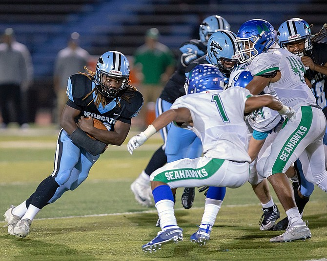 Jaquan Price #31 carries the ball for Centreville and prepares to take a hit from Mubarak Ali #1 from South Lakes.