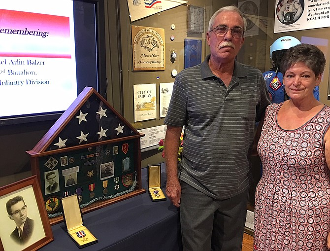 Kim and Debbie Balzer stand beside the display honoring Kim's brother Michael, including his photo, shadowbox of medals, Silver Star and Purple Heart.