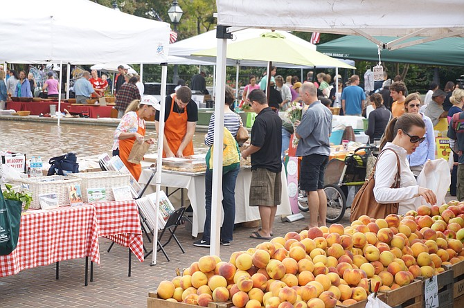 Shoppers enjoy the Old Town Farmers Market in Market Square. Visit Alexandria announced Sept. 24 that visitor spending in Alexandria grew to a record $826 million last year, a $36 million increase from the previous year.