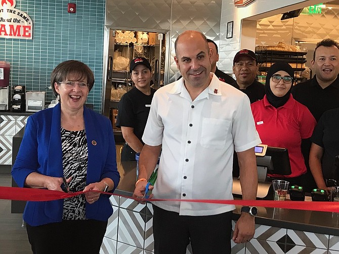 Supervisor Kathy Smith (D-Sully) and District Manager Frank Costello cut the ribbon on the new Habit Burger, while female employees (from left) Jenne Mendez and Alicia Lizama look on.