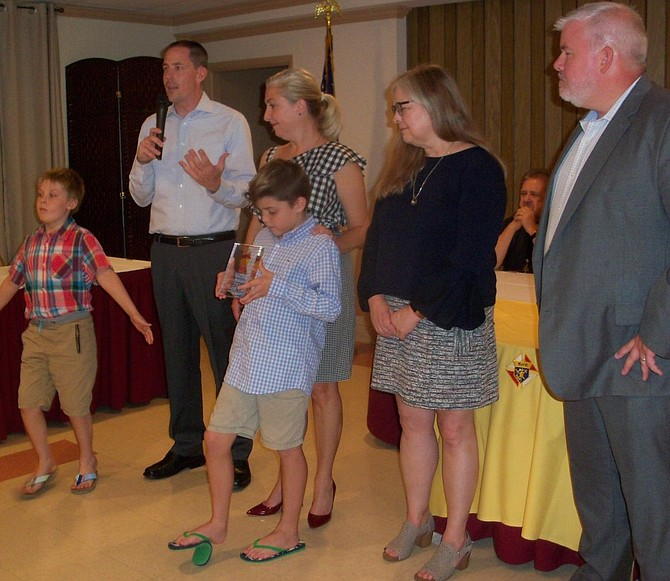 In front, Joseph Miller and James Miller hold the appreciation award conferred by Tracy's Kids to Edward Douglass White Council 2473, Knights of Columbus. In back, parents John and Teresa Miller; Tracy Councill, founder of Tracy's Kids; and Bryant Porter, chairman, Derby Day Party.