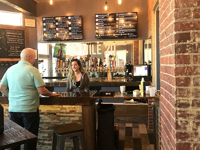 A future patron of Mile 20 stops in before the official opening to chat with the bartender, Kati Simpson, and preview the inaugural tap list.