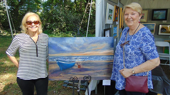 """McLean Art Society Past President Judith Landry with her """"Beached at Sunset"""" oil on canvas with Luda Del Rose, Treasurer."""