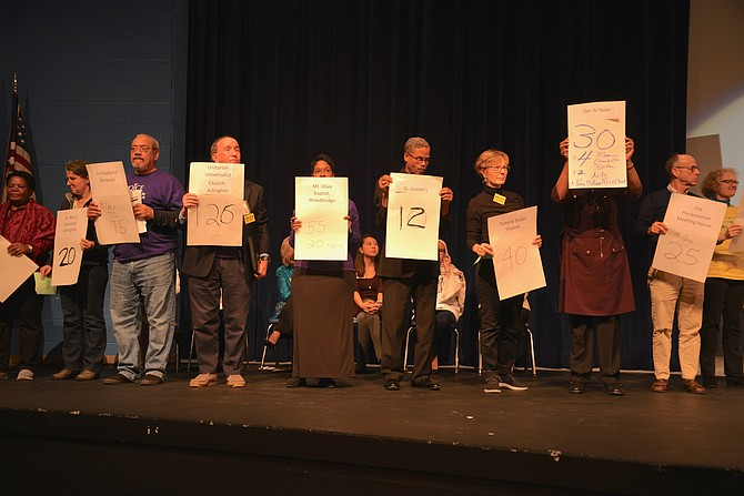 "VOICE members take to the stage at the 2018 summit with pledge posters, showing how many of their group had signed up to help Get Out the Vote and to attend the next Legislative session in Richmond. ""We will have at least 10 people per day calling for action in Richmond,"" said VOICE leadership, who also noted that the the GOTV goal of 450 volunteers had already been exceeded by 150 persons."