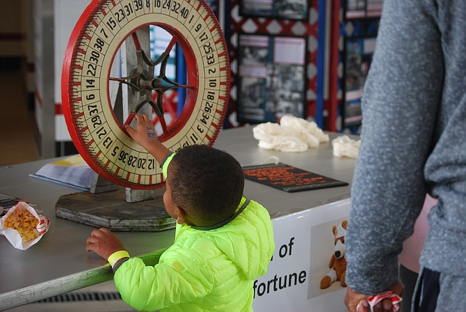 "Child spins ""The Wheel of Misfortune,"" a new game at the Great Falls Volunteer Fire Department. Kids learned what to do given a specific emergency situation."