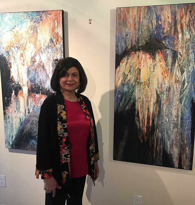 Potomac artist Nimi Trehan stands before two paintings inspired by a visit to Luray Caverns.