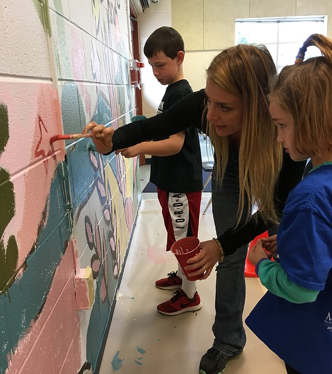 Kaylee Fefferman, 7, watches intently as Artist-in-Residence Sarah Bleiweis demonstrates a brush technique on the giant mural in the Floris School cafeteria being created by K-6th grade students.