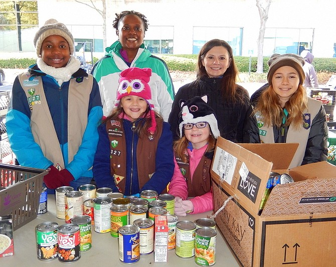 Sorting canned goods last year with Girl Scout Troop 3327 of Chantilly are (back row, from left) Brianna Mosely, mom Tanesha Mosely, Jeanine Blomberg and Ruth Moran, and (front row, from left) sisters Morgan and Phoebe Blomberg.