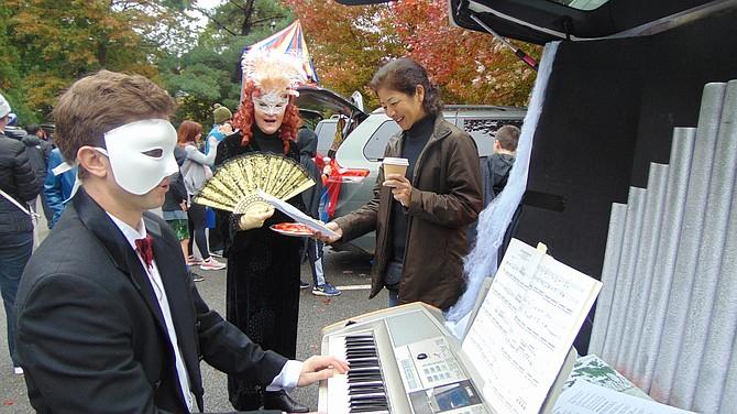 "John Nothaft, director of music, with Sally McKeown, choir member, and Yuko Takakusaki, caroler, with their ""Phantom of the Opera""-themed car."