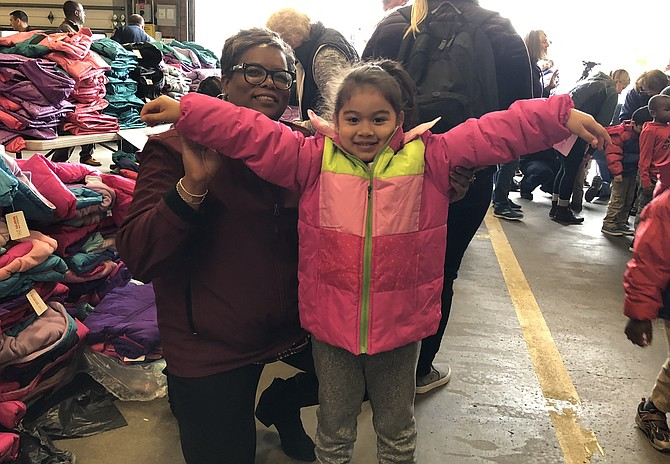 Melissa Davis helps 4-year-old Genesis show off her new coat at the Firefighters and Friends coat drive distribution Oct. 26 at Penn Daw Fire Station 11.