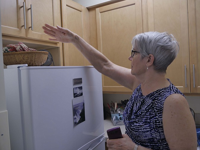 Mary MacCarthy points to the new kitchen cabinets in her renovated apartment at Culpepper Garden.