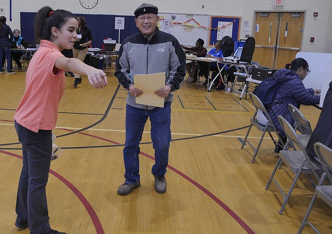 Layla Janah, a Moroccan student in T.C. Williams International Academy, serves as an election page at Samuel Tucker Elementary School polling place.