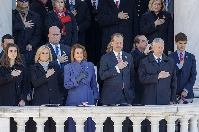 House Minority Leader Nancy Pelosi, center,  flanked by Homeland Security Secretary Kirstjen Nielsen and Department of Labor Secretary Alexander Acosta, places her hand over her heart during the playing of the National Anthem during the National Veterans Day Observance at the Memorial Amphitheater Nov. 11 at Arlington National Cemetery.