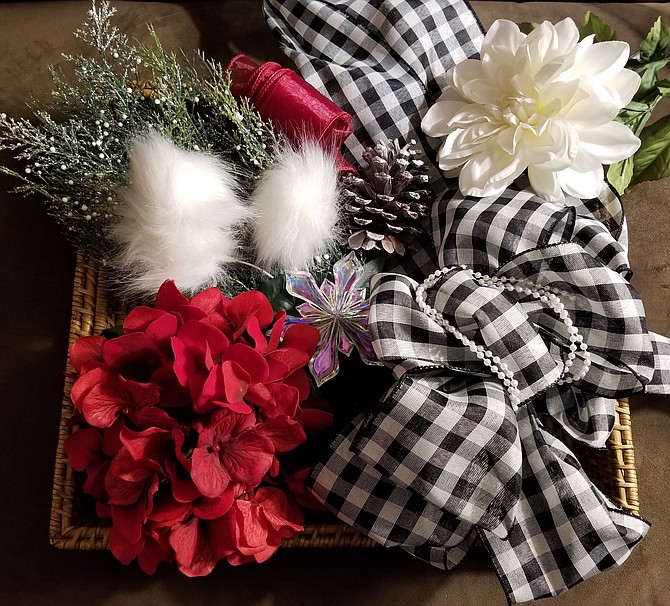 A mixture of dark red and white flowers along with holiday greenery and black and white ribbon are elements that designer Mary Biletnikoff will use to create a wreath for Light Up the Season.