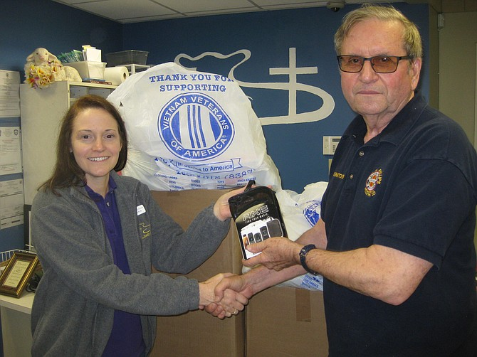 Len Ignatowski, Vietnam Veterans of America (VVA) Chapter 227 Vice President, delivers travel-size toiletries to Doris Paul, Volunteer Manager of The Lamb Center in Fairfax City, as part of the chapter's continual community and veteran outreach.