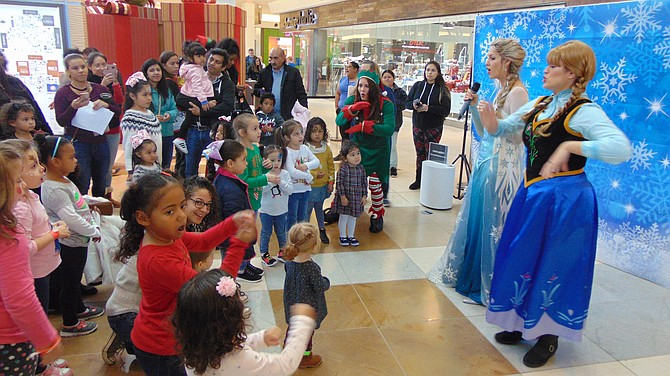 """Anna,"" aka Lizzie Allen, and the ""Frozen Queen,"" aka Jenepher Esser, of The Princess Performers delight the crowd during the Santa Fest at Springfield Town Center."