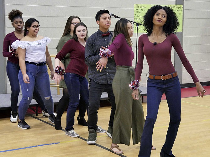 This year's traditional Thanksgiving dinner has been energized with entertainment organized by Lashawn Grace, an English teacher at Langston-Brown Continuation Program. She leads a group of students in a synchronized dance and then reaches out into the audience for partners.