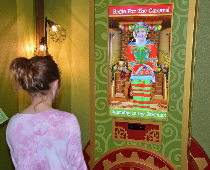 Eight-year-old Charlotte from Fairfax Station checks out her elf look in Santa's Magic Mirror.