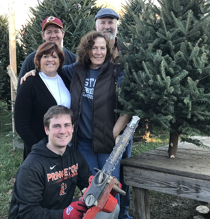 Paul and Karen Novak of Herndon (far left) purchase their annual Christmas tree one more time at the 'Elvis Tree Lot,' corner of Elden and Center Streets in Herndon. Richie Smiechowski, 18, of Herndon holds his chainsaw while Michael Hum of Herndon and Suzanne Eaton, who operates the lot, enjoy the moment too.