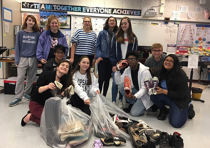 Members of the MVHS Vocal Recall advanced choir bag shoes collected from the drive: From left, back row, Nicole Duchaine, Annie Hood, Yara Ammar, Melanie Palacios Beltran and Casey Zanowic; middle row, Mark Rivera and Zachariah Pifer; front row, Erica Bartell, Laura Schmechel, Denilson Zapata, and Gopika Patel.