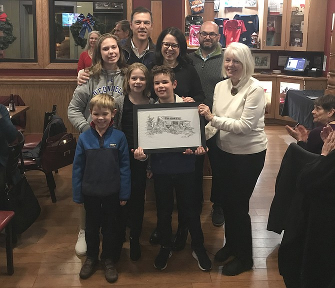 The Beebe Family receives an original pen and ink sketch of their home created by acclaimed artist Pat Macintyre (right front) who also serves as Vice President of the Board for Arts Herndon. Homes Tour Committee Co-chair, Keven LeBlanc, (right back) joins in.